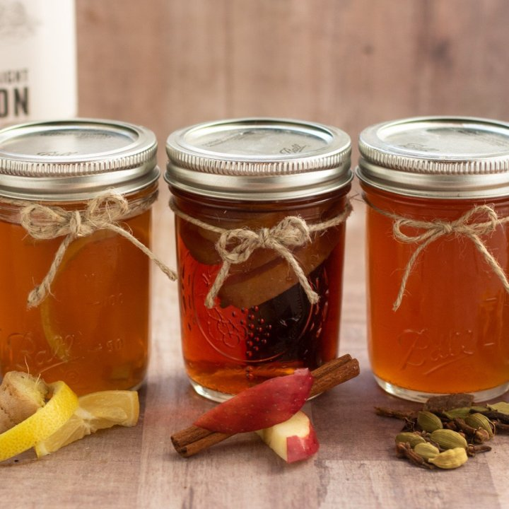 5 small mason jars with infused whiskey. The ingredients are in front of each jar like whole coffee beans, lemon and ginger, apple slice and a cinnamon stick. There's a handle of bourbon in the background.