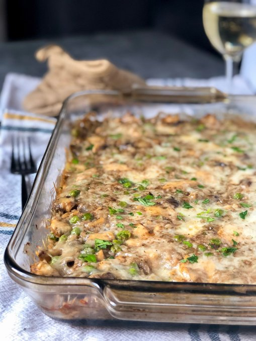 A cheesy and creamy low carb casserole dish made with cauliflower rice, brie cheese, mushrooms and peas. A glass of white wine and an oven mitt are placed in the background