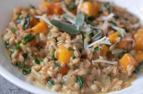 A closeup shot of a white bowl filled with farro risotto. It has pieces of butternut squash and spinach and topped with Parmesan cheese and fresh sage leaves