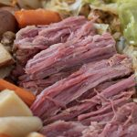 A platter with crockpot corned beef, that's tender and falling apart. Chunky potatoes, onions and carrots are on one side and fried green cabbage is on the other side. An easy and traditional St. Paddy's day recipe.