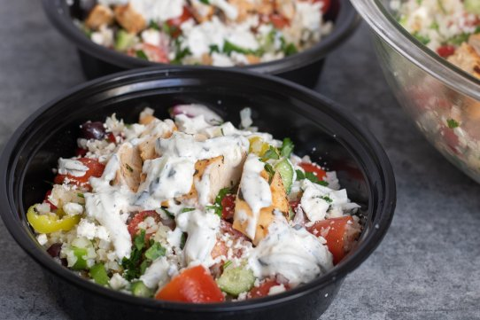 Greek chicken cauliflower rice bowls with feta cheese, kalamata olives, tomatoes, cucumbers, chickpeas and topped with tzatziki sauce. An easy and healthy meal prep recipe.