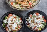 Containers filled with cauliflower Rice, Greek chicken, olives, tomatoes, cucumbers and chickpeas. They're perfectly packed for an easy meal prep for lunch on the go.