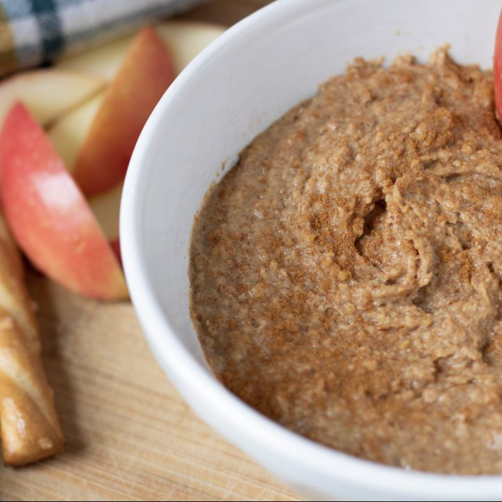 A bowl with Snickerdoodle Dessert Hummus with a slice of apple that's being dipped in the bowl. Pretzel sticks are in the background for this easy and healthy snack recipe