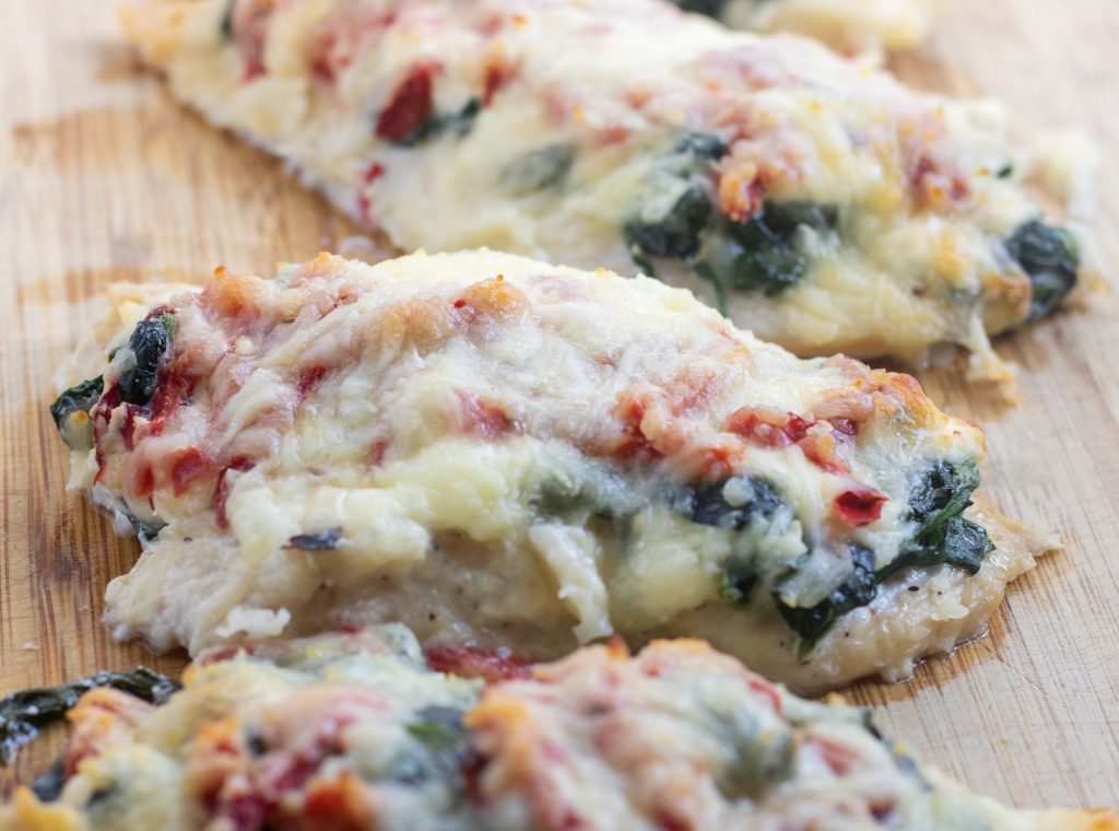 A cutting board with baked chicken that's topped with spinach and cheese.