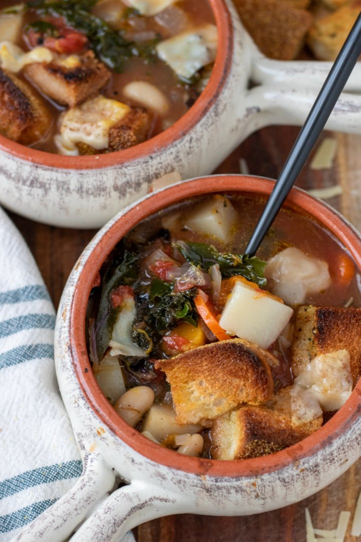 Two soup crocks filled with Tuscan ribollita soup. They're on top of a wooden surface. There's parmesan cheese sprinkled on the wood and chunks of crusty bread. There's a blue and white dish towel next to the bowls.