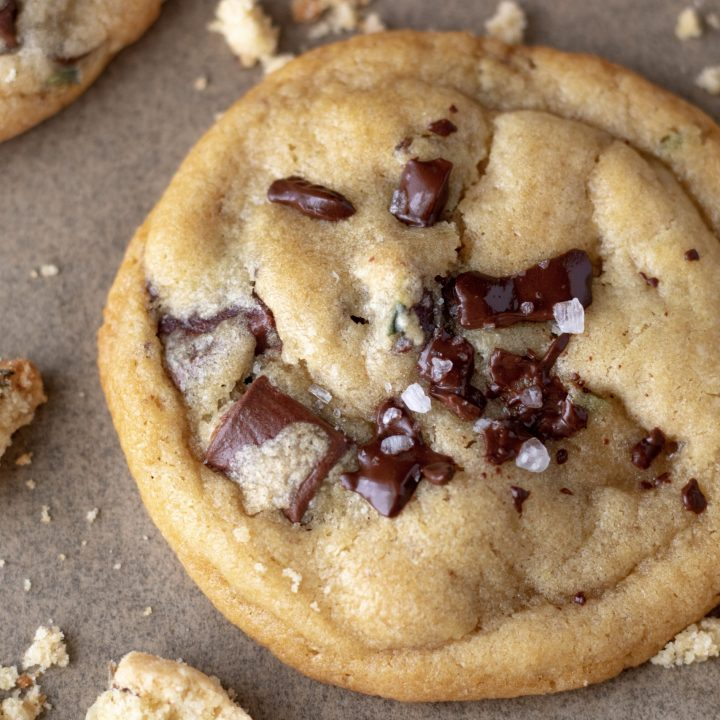 A perfectly crisp and gooey cookie made with chocolate chunks and lavender. It's on brown parchment paper and the chocolate chunks are slightly melted and there's a sprinkle of sea salt on top. There are cookie crumbs on the baking sheet surrounding the cookie.