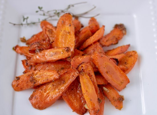 A white dish with a serving of oven roasted carrots that have been cooked with thyme garlic and ginger. They're sweet and savory for an easy veggie side dish.