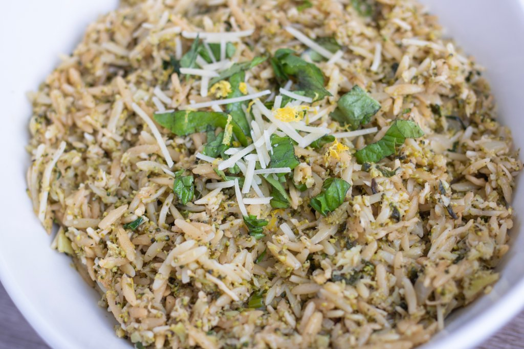 A white bowl full of orzo pasta with broccoli rice, lemon and balsamic. Fresh basil, Parmesan and lemon zest are sprinkled on the top