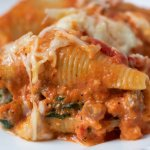 A white square dish with 3 stuffed shells that are covered in a creamy red peppers sauce and melted mozzarella cheese.