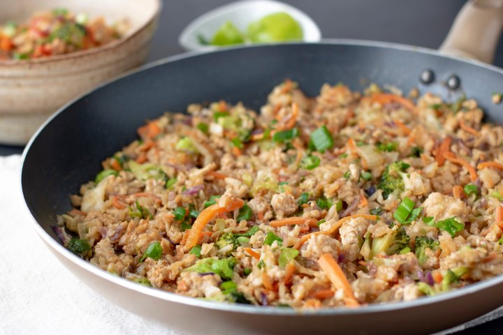 A large skillet filled with cauliflower rice stir fry with teriyaki sauce, ground turkey, carrots, cabbage and scallions. It's an easy lunch or dinner and a great meal prep recipe!