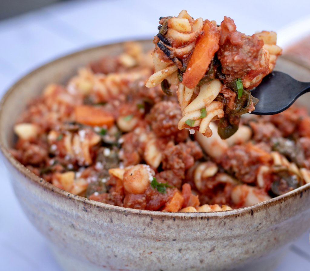A brown speckled bowl full of rotini pasta in a tomato sauce with ground turkey, cannelloni beans and spinach. There's a forkful of the pasta lifted from the bowl, it's sprinkled with cheese and fresh parsley