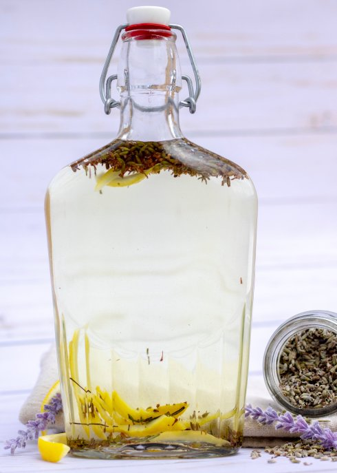 A clear bottle of vodka that's infused with lemon peel and dried lavender buds. A jar of dried lavender buds, vibrant purple lavender flowers and a fresh lemon are in the background