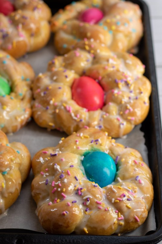 A baking sheet lined with parchment paper with 6 individual easter bread loaves that have been braided and baked. They're glazed with sugar and decorated with sprinkles. Each loaf has a colored Easter egg in the middle