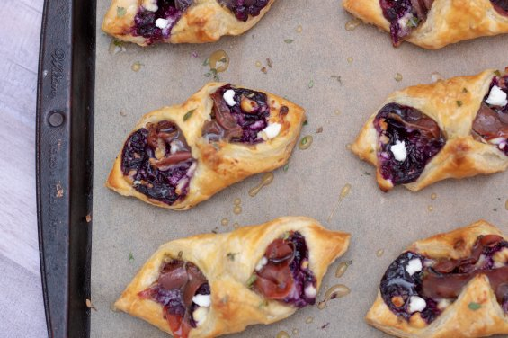 A sheet pan lined with parchment paper with puff pastry filled with blueberry filling, prosciutto and goat cheese. The pan has some drizzle of honey thyme on it with fresh thyme sprinkled on top of the appetizers.