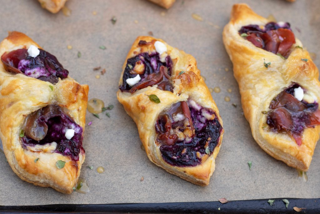 Puff pastry appetizers are golden and flaky. The inside is purple from the blueberry filling. The goat cheese crumbles are slightly browned and you can see the honey thyme dripping off the sides of the appetizers