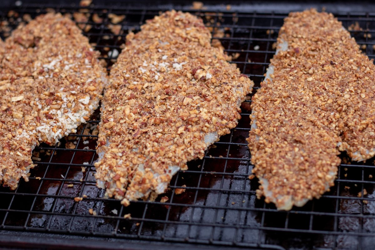 3 Pieces of white fish crusted with toasted pecans and placed on a baking sheet to be baked in the oven.