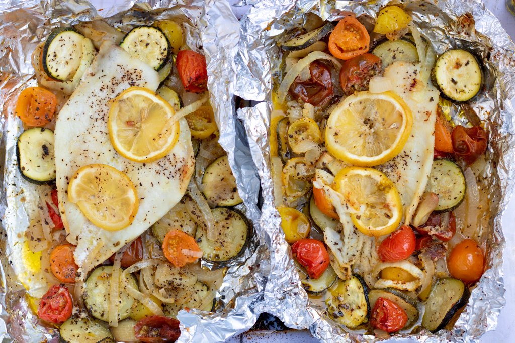 Two foil packets with white fish, colorful cherry tomatoes, sliced zucchini and sliced onions. It's sprinkled with salt and pepper and there are slices of lemon on top of the fish.