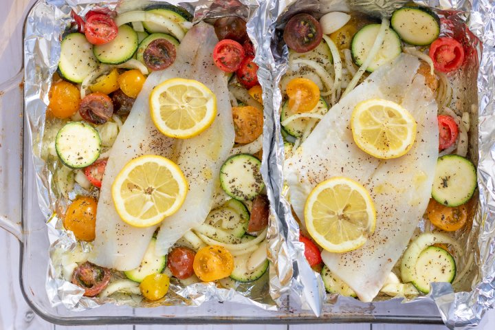 "A glass 13x9"" baking dish with two foil packets that are filled with vegetables and topped with white fish. It's to be baked in the oven for an easy family dinner that's healthy and quick to make. It's got vibrant colorful cherry tomatoes, sliced zucchini and onions."