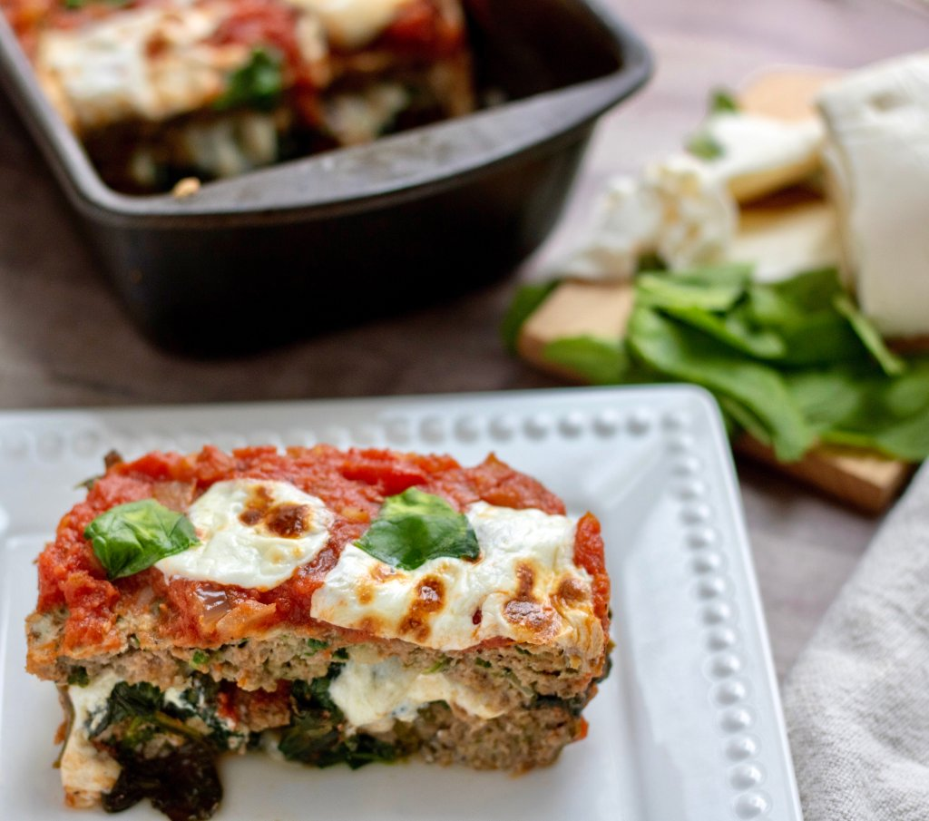 A white rectangle dish with a piece of Italian meatloaf. It's stuffed with sautéed spinach and fresh mozzarella that's melted. It's topped with marinara sauce, fresh mozzarella slices and fresh basil. A loaf pan of the meatloaf is sitting in the background. It's a quick and easy stuffed meatloaf recipe, perfect for family dinner. A small cutting board is in the background with fresh mozzarella and basil leaves