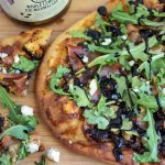 A golden crispy flatbread pizza with fig Jam, arugula, prosciutto and blue cheese crumbles. It's finished with a balsamic drizzle. A couple pizza of cut up pizza are laying next to it with the balsamic dripping and cheese crumbles on the table.
