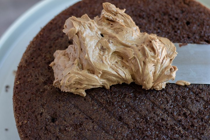 A layer of chocolate cake with a spatula smearing mocha swiss meringue buttercream on top. It's fluffy and smooth.