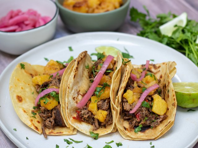 A round white plate with 3 corn tortillas that are filled with shredded beef, pineapple, pickled red onion and fresh cilantro. There's some fresh chopped cilantro on the plate and a wedge of lime. A small bowl of caramelized pineapples and another small bowl of pink pickled red onions are in the background.