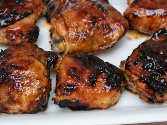 A large white rectangle platter with 6 grilled chicken thighs that have been brushed with apricot bourbon bbq sauce. The skin is crispy and slightly blackened. You can see that they're sticky and moist.