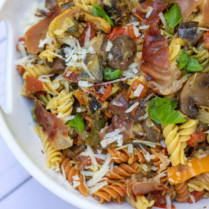 A white serving bowl filled with tri colored rotini pasta that's tossed with grilled summer vegetables, crispy prosciutto, fresh basil and parmesan cheese. You can see the roasted tomatoes, yellow squash and broccoli in the pasta.