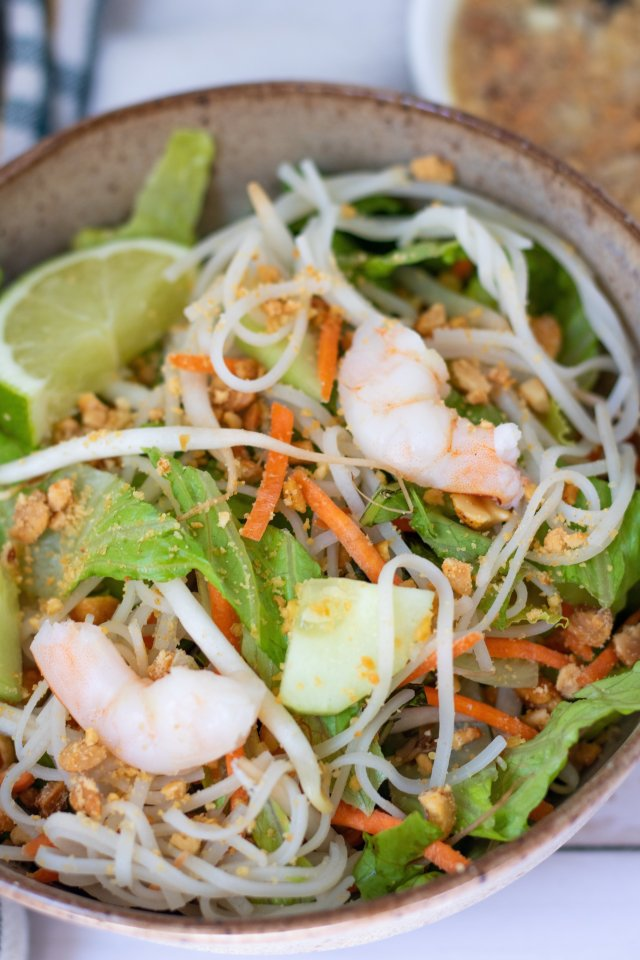 A brown speckles bowl with rice noodles, chopped lettuce, shredded carrots, cucumber, bean sprouts, basil and mint. It's topped with shrimp and a wedge of lime.