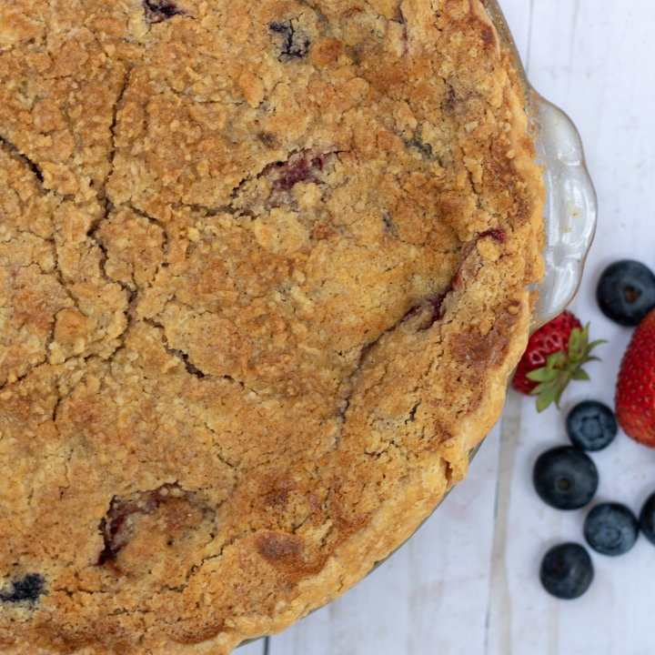 A berry pie with crumb topping. It's made with fresh summer berries like blackberries, blueberries and strawberries. The crumb topping is golden brown. There are a couple of fresh blueberries and strawberries next to the glass pie plate.