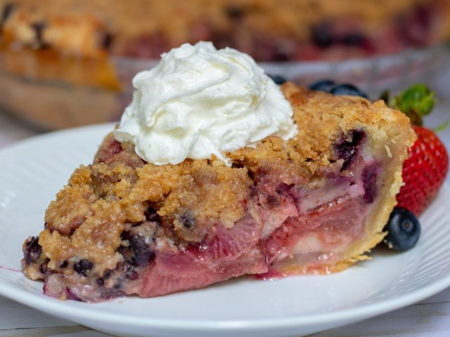 a slice of berry pie on a small white plate with blackberries, blueberries and strawberries. It's topped with fresh whipped cream and there's fresh berries on the plate.