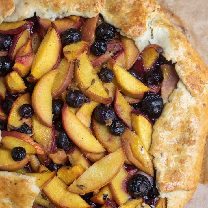 A peach blueberry crostata that's been baked on parchment paper. The crust is golden brown. There's a couple of fresh blueberries with dried lavender and a purple lavender flower in the background.