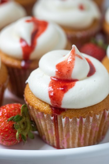 A cupcake with whipped cream cheese frosting with strawberry reductions dripping down the side. There's fresh strawberries on the cake stand with the cupcake.