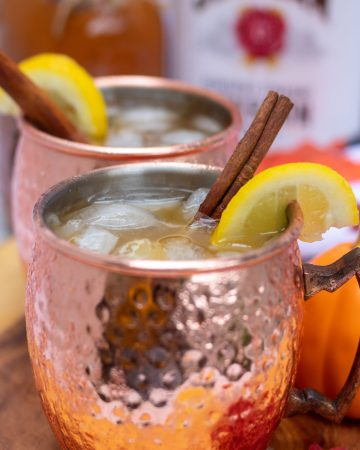 A pumpkin moscow mule in a copper mug. You can see the ice in the cup and it's garnished with a lemon wedge and cinnamon stick. There's a red fall leaf and pumpkin next to the cup. You can see the bottle of whiskey and mason jar of homemade pumpkin butter in the background.