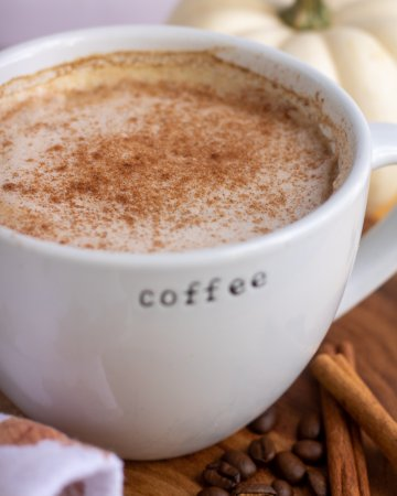 """A large white coffee mug that says """"coffee"""" filled with pumpkin spice latte and sprinkled with cinnamon. There's cinnamon sticks and coffee beans in the background with a small white pumpkin"""