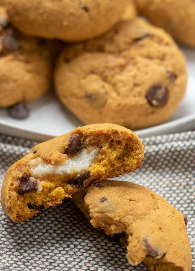 A pumpkin chocolate chip cookie broken in half where you can see the cream cheese filling. There's a beige plate of cookies in the background.
