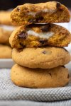 A stack of pumpkin chocolate chip cookies where the top cookie is in half and you can see the cream cheese filling. You can see a beige plate of cookies in the background