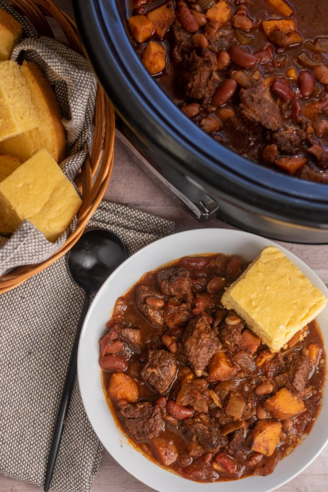 An overhead shot of a white bowl of chili with a side of cornbread, a black crockpot and a basket full of cornbread. There's also a black spoon next to the bowl of chili