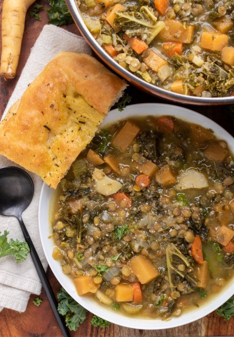 A wooden board with a white bowl of vegetable lentil soup. There's a piece of golden crusty bread next to it, a black round spoon and chopped kale sprinkled on the wooden board. A larger dutch oven pot of soup is in the background.