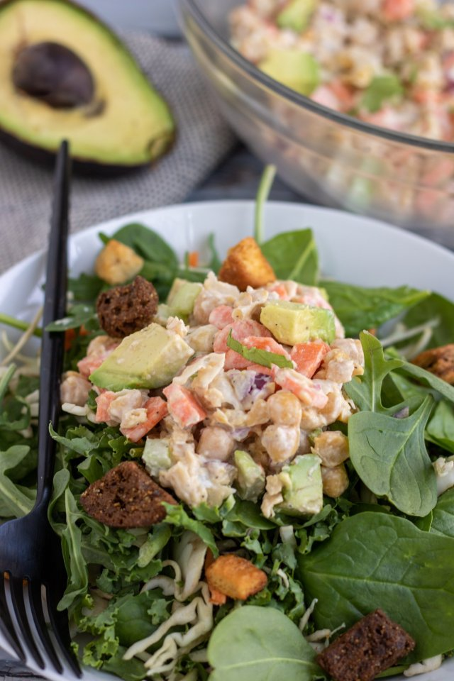 A bowl of mixed green salad topped with mashed chickpea salad. There's croutons on the salad with a black fork on the dish. There's a large bowl of the chickpea salad in the background with half of an avocado