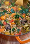An orange dutch oven pan on top of a wooden surface filled with color vegetable barley soup. You can see the orange tomaotes, mushrooms and broccoli
