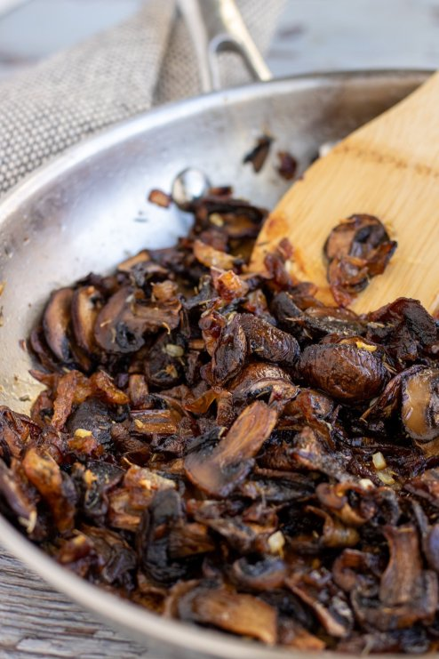A stainless steel saute pan with caramelized mushrooms and onions with a wooden spoon scooping them up. The mushrooms are a deep brown and slightly crispy on the edges