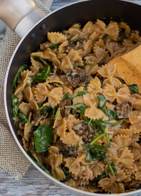 A large saucepan with bowtie pasta in a creamy balsamic sauce with mushrooms and spinach. There's a wooden spoon taking a scoop of the pasta out of the pan.