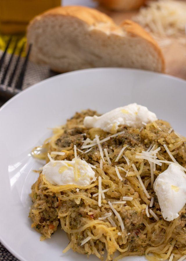 A white pasta bowl with spaghetti squash topped with broccoli pesto and dollops of ricotta cheese. It's drizzled with olive oil and grated parmesan cheese. There's a fork next to the bowl and a slice of Italian bread in the background