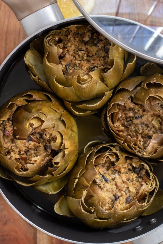 A large saucepan with 4 artichokes in it. The lid is resting on the side of the pan. The artichokes are steamed and tender with a breadcrumb stuffing