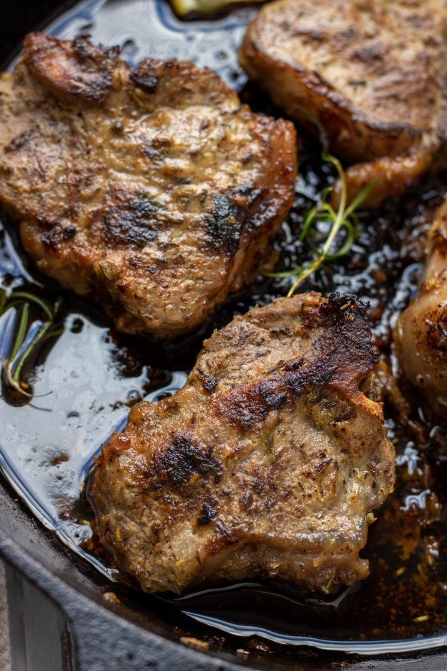 A cast iron pan with seared lamb chops in it. They're golden brown with sprigs of fresh rosemary in the pan.