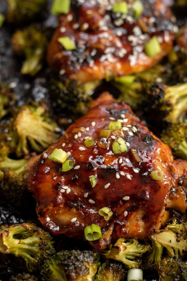 A black metal sheet pan topped with roasted broccoli, and Asian chicken thighs. They're browned and topped with sesame seeds and scallions.