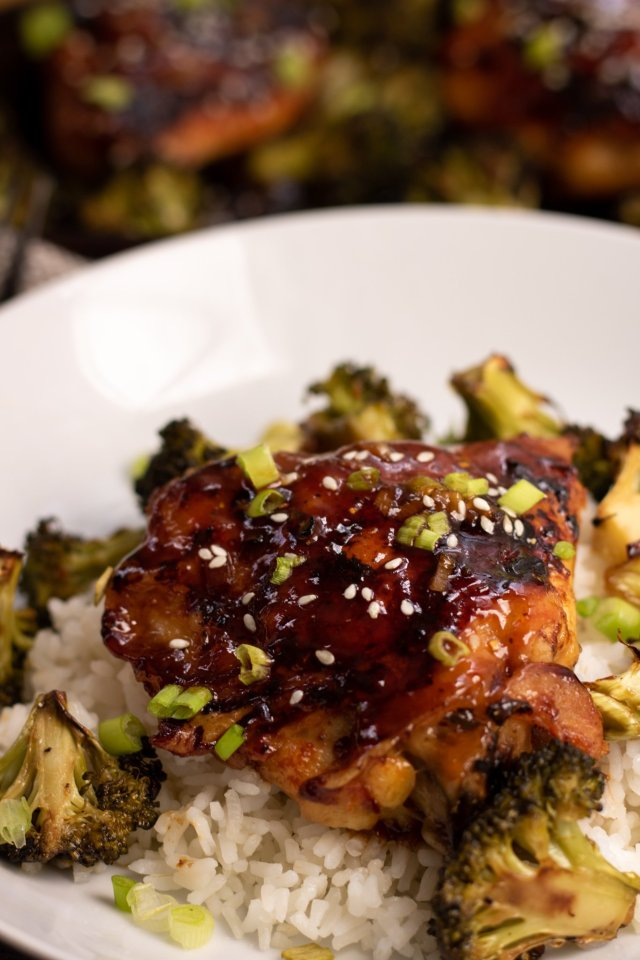 A shallow white bowl with white rice, roasted broccoli and a piece of crispy chicken thighs that have an Asian sticky glaze on them. The chicken is browned and sprinkled with sesame seeds and scallions. There's a sheet pan of chicken in the background.