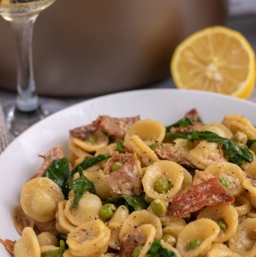A white pasta bowl filled with orecchiette pasta with peas, crispy prosciutto and arugula. There's a glass of white wine and half a lemon in the background.