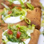 Three chimichangas that are topped with sour cream, shredded lettuce and guacamole. They're dark brown and crispy from the air fryer.